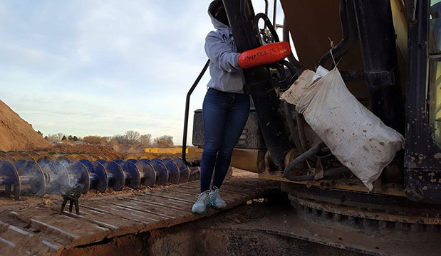 An Indigenous Water Protector with the Frontera Water Protection Alliance locks to a track hoe, a machine being used to construct Energy Transfer Partner's Comanche Trail pipeline in El Paso County, on Friday, January 13, 2017. (Photo: Courtesy of Frontera Water Protection Alliance)