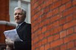 WikiLeaks founder Julian Assange addressing the media and holding a printed report of the judgement of the UN's Working Group on Arbitrary Detention on his case from the balcony of the Ecuadorian Embassy in central London on February 5, 2016 (AFP Photo/BEN STANSALL )