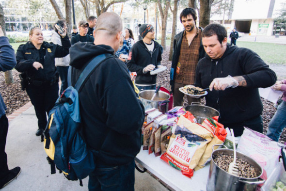 A volunteer serves food as police linger nearby.Anthony Martino