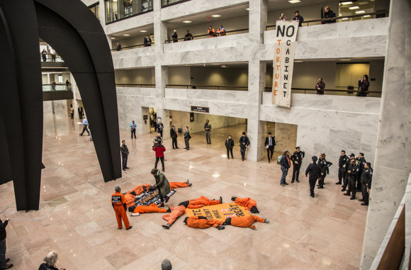 Witness Against Torture protests in the rotunda of the Hart Senate Office Bulding with banner drop and die-in. January 2017