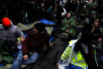 Demonstrators chant while in their sleeping bags outside of Goldman Sach's Lower Manhattan headquarters during a protest against the Wall Street bank's ties to the incoming administration of U.S. President-Elect Donald Trump in New York, U.S., January 17,2017. REUTERS/Bria Webb