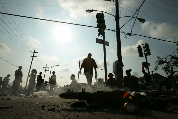 People wait for assistance after being rescued from their homes a day earlier in the Ninth Ward as a small fire burns after Hurricane Katrina, Aug. 31, 2005, in New Orleans. Photo: Mario Tama/Getty Images