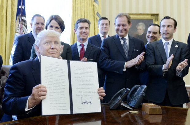 Flanked by business leaders, President Trump signed his latest order to begin rolling back federal regulations. Credit: Getty Images