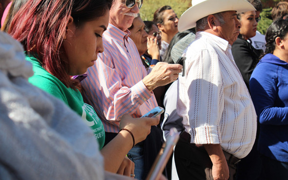 Protestors use their cell phones to call Sen. John McCain and ICE Director Carter asking for Guadalupe Garcia De Rayos' release. (Photo by Charlene Santiago/Cronkite News)