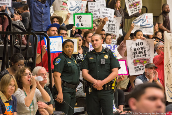 Law enforcement officers next to pipeline opponents at the Louisiana DNR's permit hearing for the Bayou Bridge project on February 8.