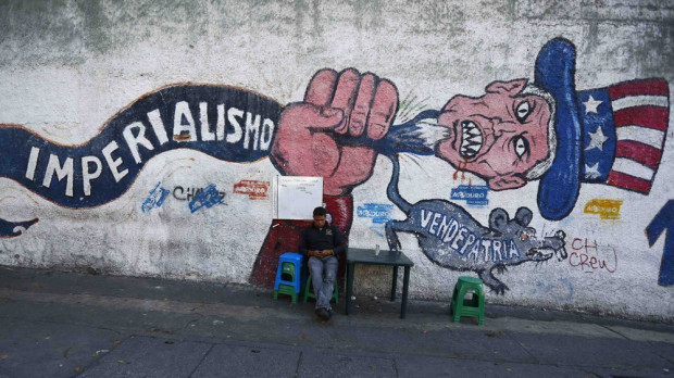 A man sits in front of a mural in Caracas, Venezuela | Photo: Reuters