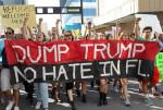 "Protesters hold a ""Dump Trump"" sign as they march in downtown Miami on Saturday, Feb. 4, 2017. Roberto Koltun rkoltun@miamiherald.com"