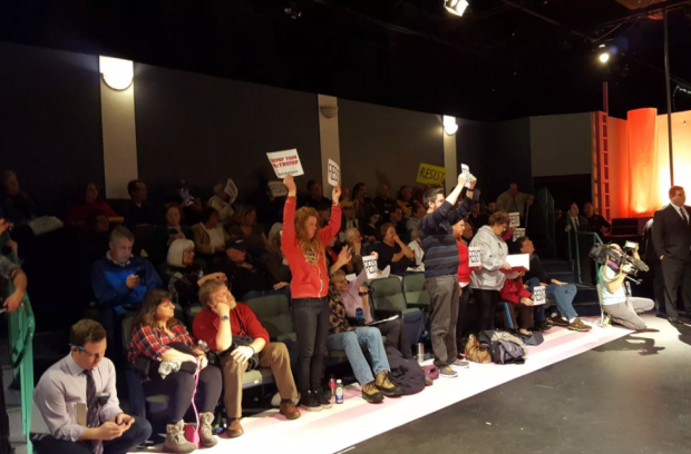 """Several people standing with """"resist"""" signs in @RepMcClintock meeting. @KQEDnews – photo by Katie Orr KQED"""