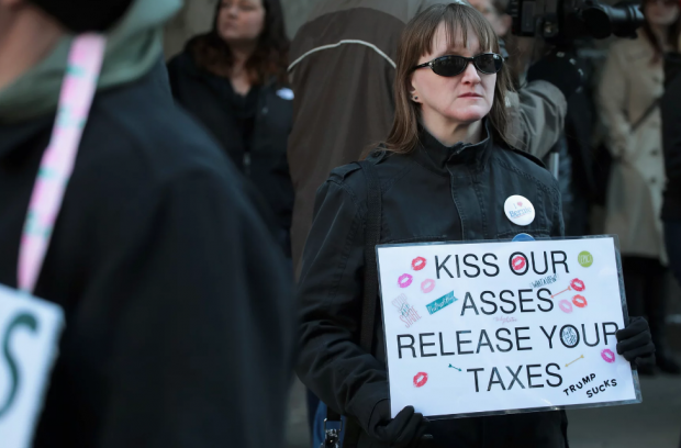 A protester urges Donald Trump to release his own tax returns. Photograph: Scott Olson/Getty Images