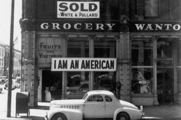 """Oakland, Calif., Mar. 1942. A large sign reading """"I am an American"""" placed in the window of a store on December 8, the day after Pearl Harbor. The store was eventually closed after the issuance of E.O. 9066. (Photo: Dorothea Lange)"""