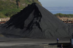 Two workers walk in front of coal accumulated at a thermal power plant in Abono, near Gijon, northern Spain, June 5, 2012. REUTERS/Eloy Alonso