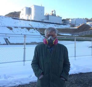 Arnie Gundersen wearing his respirator in front of the nuclear waste incinerator.