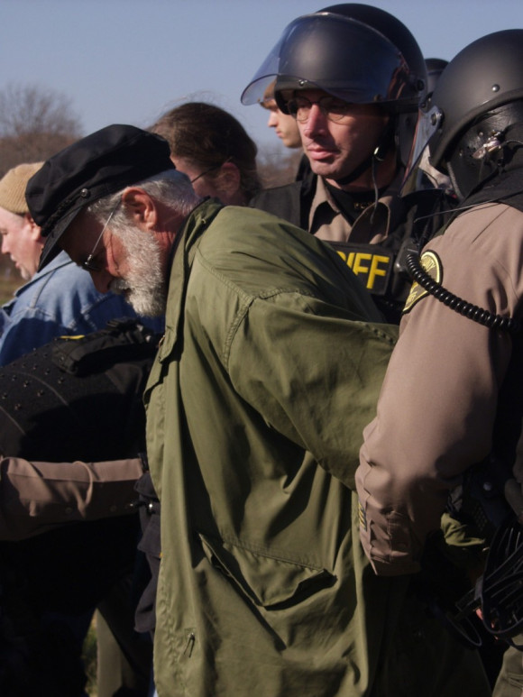 Frank Cordaro arrested while protesting at Camp Dodge in Johnston, IA. Photo courtesy of Des Moines Catholic Worker.