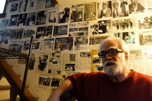 Frank Cordaro standing near the entrance to the Bishop Dingman House, one of the Catholic Worker Houses in Des Moines. The wall behind him is decorated with news-clippings of famous protesters. By Hannah Little