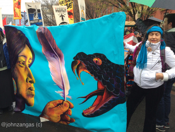 Cassandra displays a painting telling a story about the resistance at Standing Rock. Photo: John Zangas
