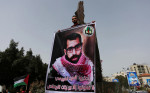 A Palestinian in Gaza City carries a poster of Bassel al-Araj on 12 March. Ashraf Amra APA images