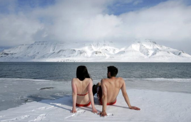 Climate activists Lesley Butler and Rob Bell (R) 'sunbathe' on the edge of a frozen fjord in the Norwegian Arctic town of Longyearbyen April 25, 2007. REUTERS/Francois Lenoir/File Photo