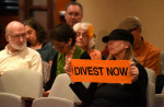 An activist calls for divestment at a Portland City Council meeting last week. The council's decision to divest from all corporations was a victory for activists organized along intersectional lines. (Photo: Doug Yarrow)
