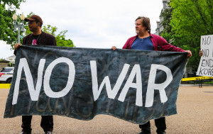 Christopher Glenn and Kevin Zeese holding No War banner at White House and Eisenhower Executive Office Building April 27, 2017. Photo by Anne Meador, DC Media Group.