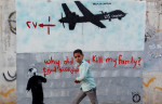 Yemeni boy walking past mural. by Mohammed Huwais for AFP and Getty Images