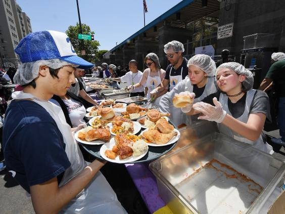 Volunteers from the Midnight Mission help feed the homeless and poor during its annual Easter/Passover celebration at Skid Row in Los Angeles, California (Getty Images)
