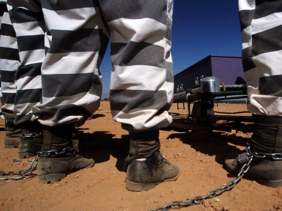 Female jail inmates are chained together as they bury cadavers at Maricopa County's pauper's graveyard in Phoenix, Arizona (Joe Raedle/Liaison)
