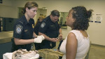 US Customs and Border Protection (CBP) officers check a passenger's luggage and documents. CBP R