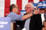 Senator Bernie Sanders, right, is embraced by Democratic National Committee chair Tom Perez at a party rally in Mesa, Arizona, 21 April. (Gage Skidmore)