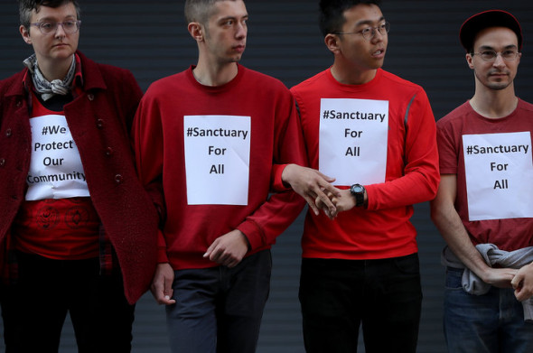CREDIT: JUSTIN SULLIVAN/GETTY IMAGES Protesters stand arm-in-arm to block the entrance to a U.S. Immigration and Customs Enforcement office in San Francisco.