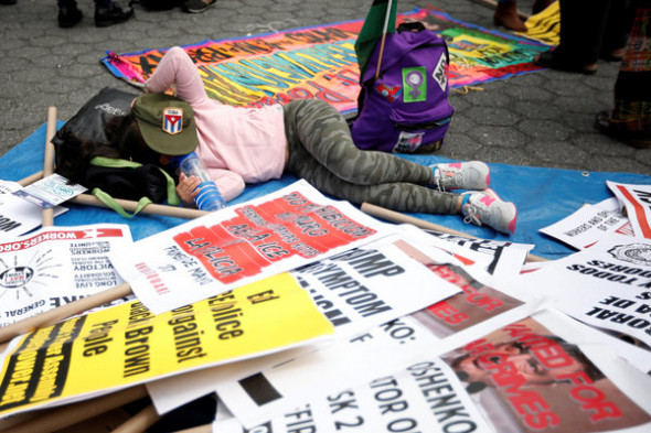 Mike Segar / Reuters A demonstrator rests among signs during a May Day protest in New York, U.S. May 1, 2017.