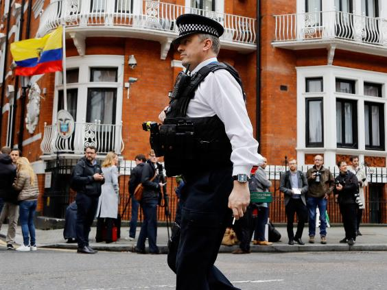 A police officer walks past people gathering outside the Ecuadorian embassy in London on 19 May (AP)