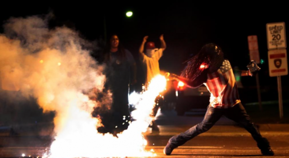 Edward Crawford in iconic Ferguson protest photo. By Robert Cohen for St. Louis Post-Dispatch and AP; August 13, 2014