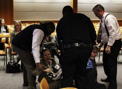 Fred Bucher, is head of the securities operation center at the FCC on the right after he tackled Margaret Flowers and Kevin Zeese and threw them to the ground.