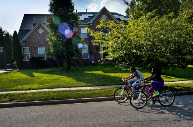 Harmony Bryant, 13, and Jayla Bryant, 10, ride their bikes in their neighborhood along Hillrod Lane on Aug. 5, 2014 in Kettering, Maryland. The Bryants were part of an expanding black middle class that was accumulating wealth in Prince George's County but the housing crash stripped more than half the value from their home. (Photo by Michel du Cille/The Washington Post via Getty Images)