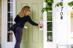 Margaret Flowers puts door hanger featuring Ajit Pai on his neighbors door, by Anne Meador May 7, 2017