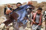 A man displays the bloodied shirt of a child victim at the rubble of houses destroyed by an Saudi airstrike in the Okash village near Yemen's capital, Sanaa. Saudi Arabia's bombing of Yemen continues with the backing and support of the U.S. (Photo:Reuters)