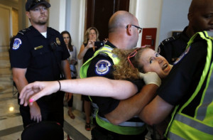 Stephanie Woodward, of Rochester, NY, who has spina bifida and uses a wheelchair, is removed from a sit-in at Senate Majority Leader Mitch McConnell's office as she and other disability rights advocates protest proposed funding caps to Medicaid, Thursday, June 22, 2017, on Capitol Hill in Washington. CREDIT: AP Photo/Jacquelyn Martin