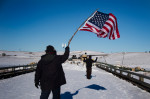A protester waves an American flag as an activist approaches the police barricade with his hands up on a bridge near Oceti Sakowin Camp on the edge of the Standing Rock Sioux Reservation. Photographer: Jim Watson/AFP via Getty Images