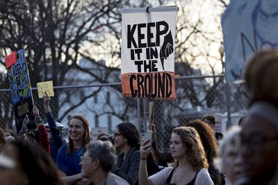 A demonstrator holds a sign during a Dakota Access pipeline protest in Washington, D.C. Photographer: Andrew Harrer/Bloomberg