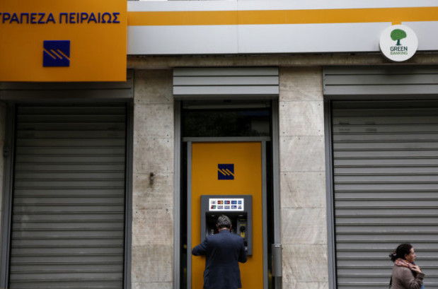A man makes a transaction at an automated teller machine (ATM) of a Piraeus Bank branch in Athens, Greece. (AP/Yorgos Karahalis)