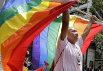 Randy Burns, co-founder of Gay American Indians, hoists rainbow flags during the Pride parade in San Francisco on Sunday. (Jeff Chiu / AP Photo)