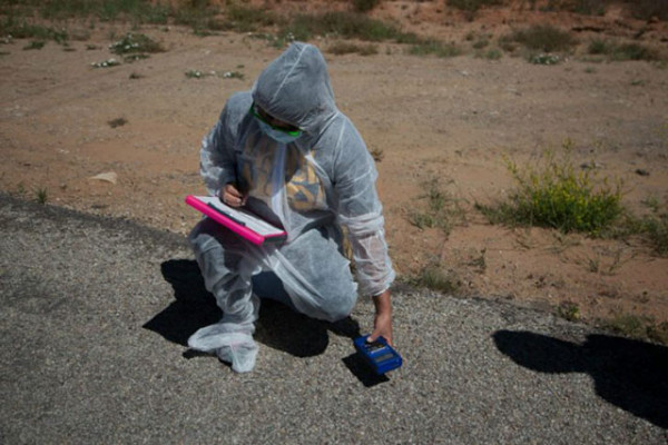 "Leona Morgan, representative from ""Haul No!"" and co-founder of the organization ""Dine No Nukes,"" takes radioactivity readings around the White Mesa Mill. Last year there was a radioactive spill in this area. (Photo: Garet Bleir)"