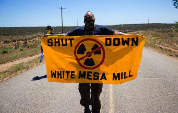 "Bobby Mason, representative of ""Haul No!"", carries a ""Shut Down White Mesa Mill"" sign through the gates of the mill. (Photo: Garet Bleir)"