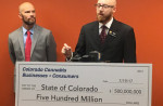 """MASON TVERT / VS STRATEGIES State Rep. Jonathan Singer (D) accepts a novelty check for half a billion dollars from """"The Cannabis Community"""" on Wednesday."""