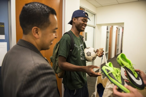 DAMON DAHLEN/HUFFPOST Attorney Cesar Vargas watches as his client Ivan Ruiz is given soccer shoes at the Safe Passage Project offices in Manhattan on Tuesday.