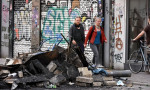 Residents in the Schanzenviertel district of Hamburg pass by a pile of burned debris following looting and rioting by G20 protesters. Photograph: Zuma Wire/Rex/Shutterstock