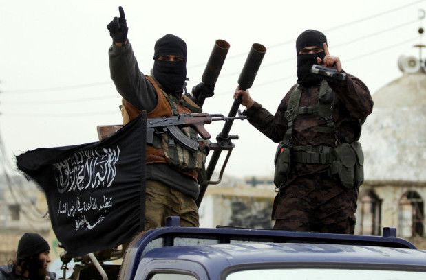Members of al-Nusra Front gesture as they drive in a convoy touring villages in the southern countryside of Syria's Idlib province, Decembe, 2014. (Photo: Khalil Ashawi/Reuters)