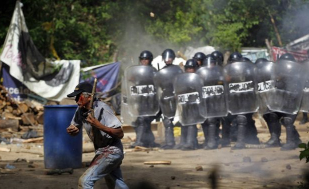 An injured protester flees as riot police use tear gas and batons to disperse a demonstration against the Tambor mining project at La Puya on May 23, 2014. (Reuters/Jorge Dan Lopez)