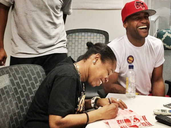 Shantel Walker, a Papa John's employee and leader of the Fight for $15, signs a card to join Fast Food Justice, a new labor organization in New York City. (WNV/Fast Food Justice)