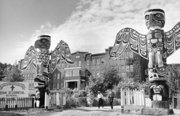 REUTERS/DEPARTMENT OF CITIZENSHIP AND IMMIGRATION-INFORMATION DIVISION/LIBRARY AND ARCHIVES CANADA Students walk between two totem poles at St. Michael's Indian Residential School in Alert Bay, British Columbia, in a 1970 photo.